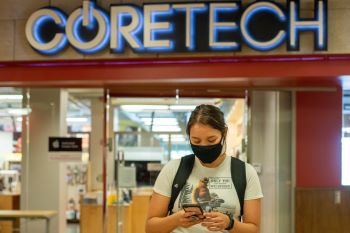 Girl using phone and wearing a mask in front of the CORETECH store
